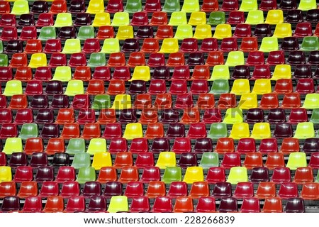 Detail with empty colored sports arena tribunes on a football stadium - stock photo