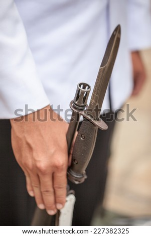 Detail with the hand of a soldier on a bayonet rifle in rest position during a military parade. Thailand. Bangkok. Wat Phra Keo - stock photo