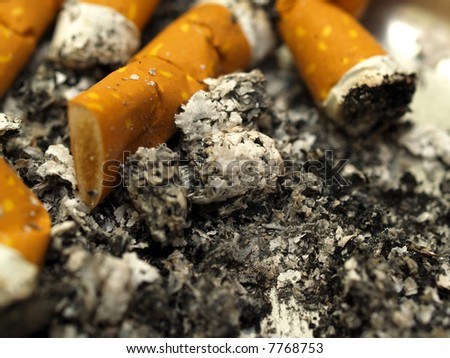 Detailed close-up macro of cigarette and ash in ashtray - stock photo