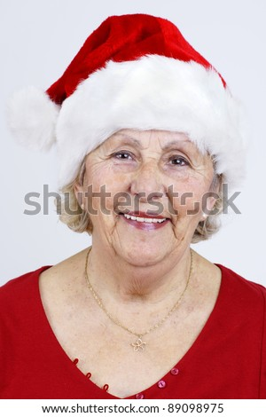Detailed close-up of a grandmother smiling as she prepares for Christmas with her red Santa Claus hat. - stock photo