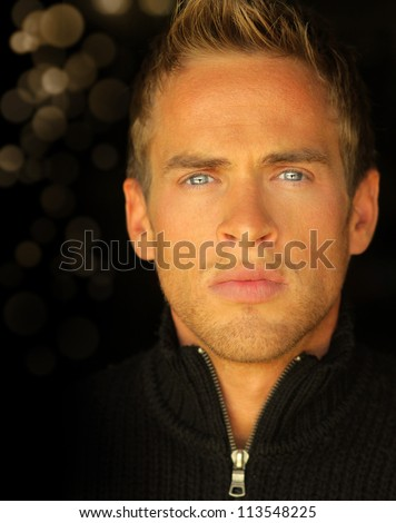 Detailed close up portrait of a young blond man with beautiful blue eyes - stock photo
