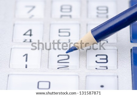 Detailed closeup of calculator display with pencil and numbers. - stock photo