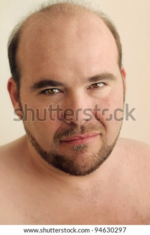 Detailed closeup portrait of a mature balding man with beard against warm neutral background - stock photo