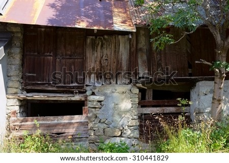 Detailed facade view of a ramshackle ruined barn of boulders, wood and rusty metal pan plate roof