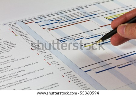 Detailed Gantt Chart showing Tasks, Resources and Notes. Includes a pen being held by a man on the right. - stock photo