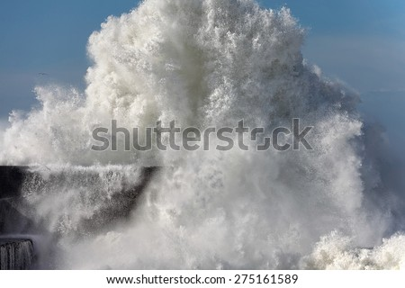 Detailed huge wave breaking against a pier - stock photo
