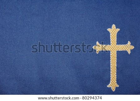 Detailed image of embroidered gold cross on blue velvet background. With space for your text overlay - stock photo