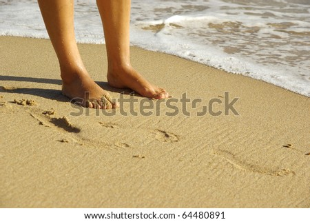 Detailed image of woman's feet on a sand beach. - stock photo