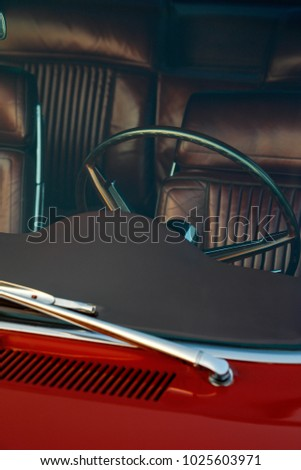 detailed image showing the steering wheel and brown seats of an old car in vintage style