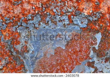 detailed macro shot of a patch of paint flecked rust, strong colours and interesting textures. - stock photo