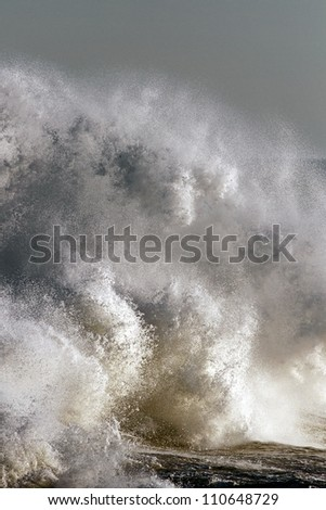 Detailed photo of a big stormy wave crashing over Portuguese Coast - stock photo