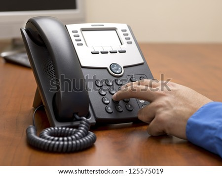 Detailed shot of a human hand dialing number on landline phone on office desk. - stock photo