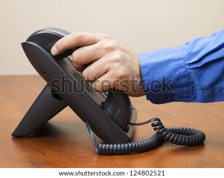 Detailed shot of a man holding land line phone receiver on wooden desk.