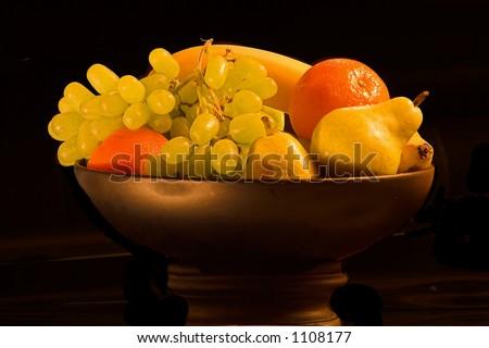 detailed still life fruit in bowl against black background. - stock photo