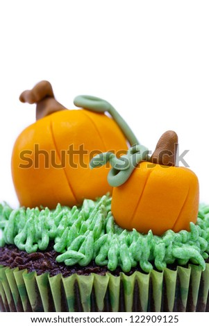 Detailed view of a Cupcake with pumpkin miniature displayed against white background. - stock photo