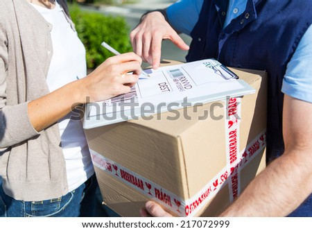 Detailed view of a customer signing delivery note - stock photo