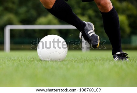 Detailed view of a footballer / soccer player dribbling the ball. Selective focus. - stock photo