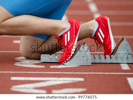 Detailed view of a sprinter in the starting blocks - stock photo