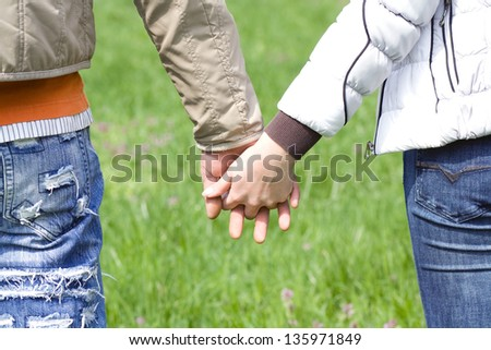 Detailed view of a young couple holding hands