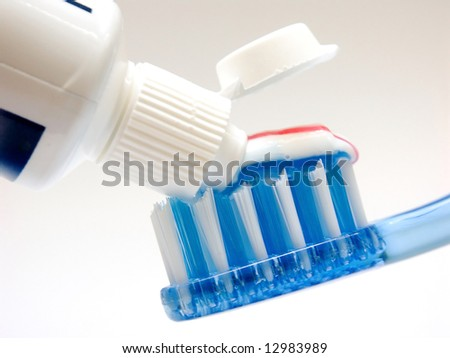 Detailed view of application of toothpaste to the bristles of the toothbrush. Dental hygiene using clean. Caring for healthy teeth.