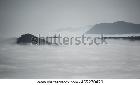 Detailed view of beautiful clouds and fog below mountain range, dark image in black and white - stock photo