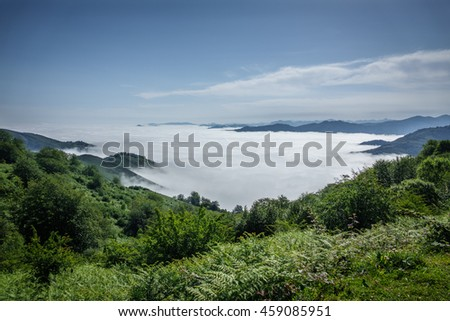 Detailed view of beautiful clouds and fog below mountain summits and covering valley