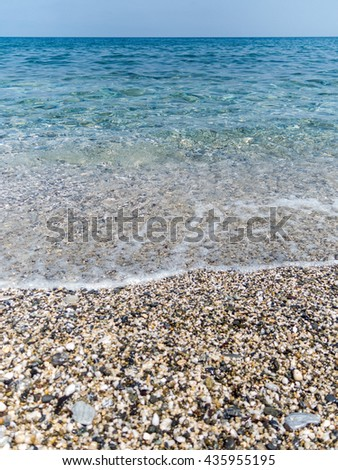 Detailed view of gentle waves lapping against a pebbly beach in Greece. Image depicts calm, peace and tranqulity associated with relaxing summer holidays in the Mediterranean - stock photo