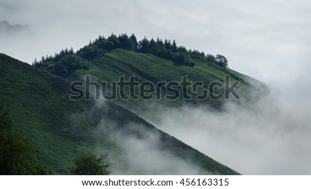 Detailed view of green mountains over the clouds - stock photo