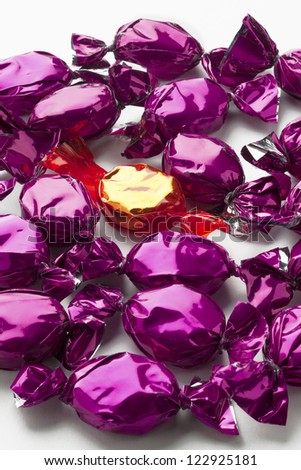 Detailed view of shiny golden hard candy surrounded by purple hard candies over white background. - stock photo