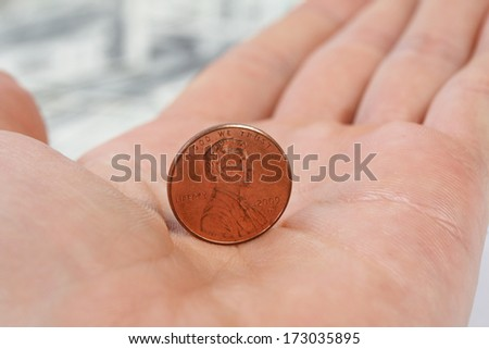 Detailed view standing penny on male hand on background of money american hundred dollar bills  - stock photo