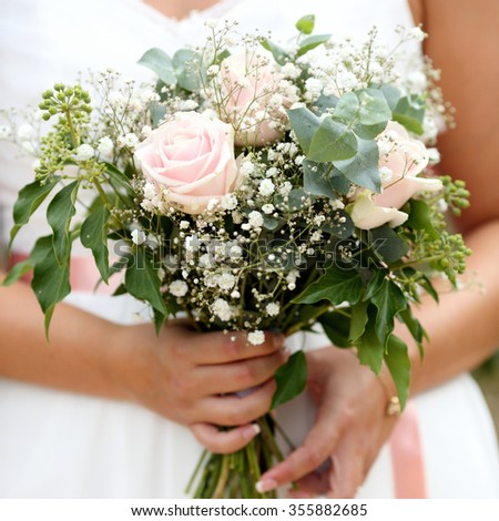 Details of a beautiful and luxuary wedding bouquet in front of a wedding dress.
