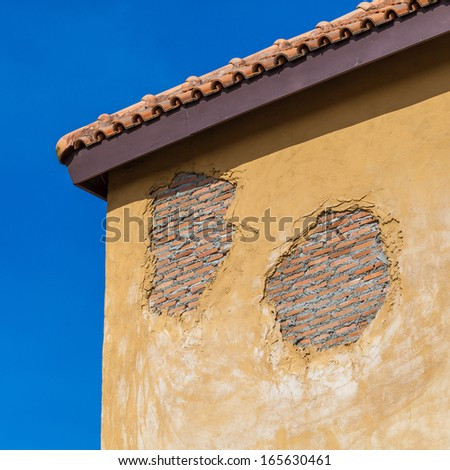 Details of a concrete yellow divider wall falling apart - stock photo