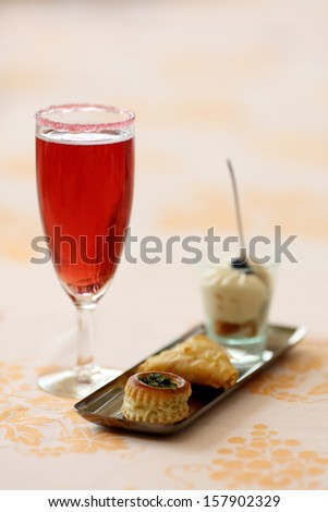 Details of a glass of kir royal and amuse bouche.