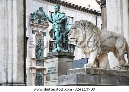 details of a stone lion sculpture and Statue of Graf V Tilly at the Odeonsplatz - Feldherrnhalle in Munich Germany - stock photo