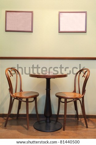 Details of an interior of a small cafe. Just chairs, empty frames and tables. - stock photo