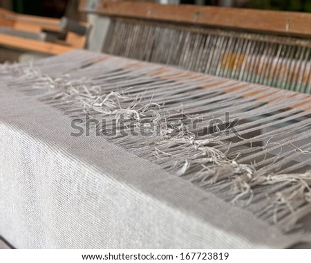 Details of an old fashioned fabric loom weaving threads together. - stock photo