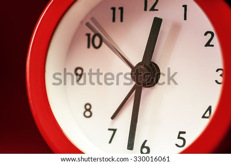 Details of an old red watch on red background.  - stock photo