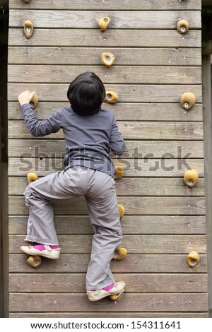 Details of an outdoors climbing girl on a climbing wall for kid