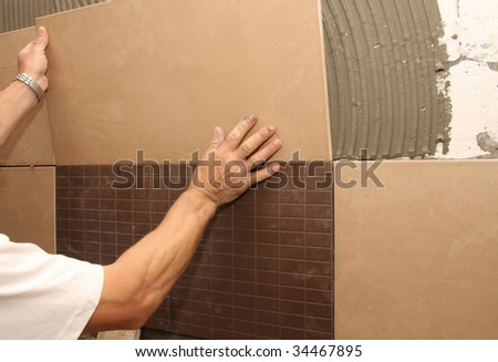 details of laying ceramic tile on wall - stock photo