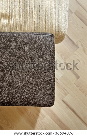 Details of leather sofa headboard on Wooden floor - stock photo