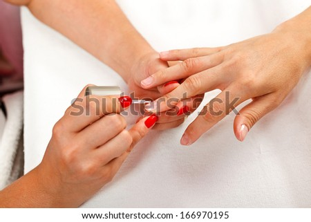 Details of nail painting with transparent nail polish in beauty salon.  - stock photo