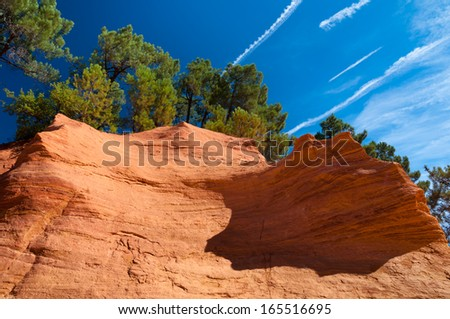 Details of orange rock formation and trees under blue sky on Le Sentier des Ocres in Roussillon - France - stock photo