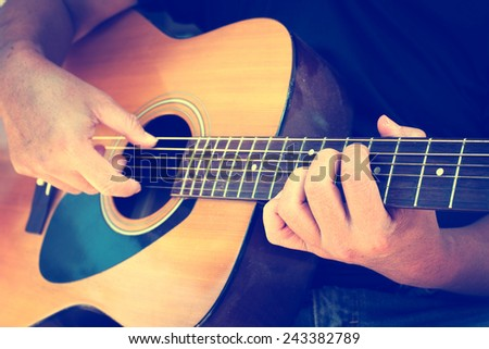Details of performer man hands playing acoustic guitar musical, vintage retro photo - stock photo