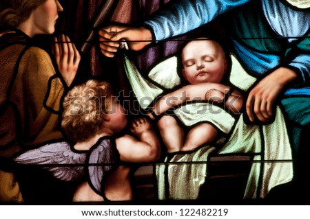 Details of stained glass window depicting baby Jesus at Christmas - stock photo