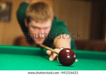 Details of the game of billiards. Red ball in the center of the frame. Player aiming cue in a billiard ball. Blurred person in the background. - stock photo