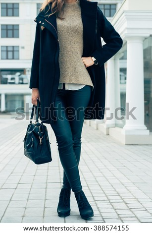 Details of women's clothing. A woman in a sweater, black coat and pants holding a handbags while walking in the city. - stock photo