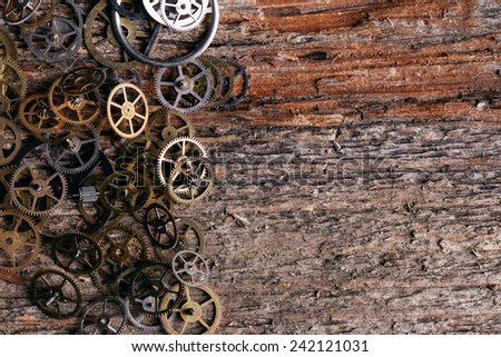 Details, technology. Heap of small gears on a wooden table - stock photo