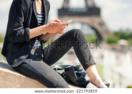 Deteail of young woman using mobile phone in front of the Eiffel Tower. Paris, France. Filtered image. - stock photo