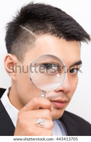 Detective Business asian man Looking At camera Through Magnifying Glass close up on white