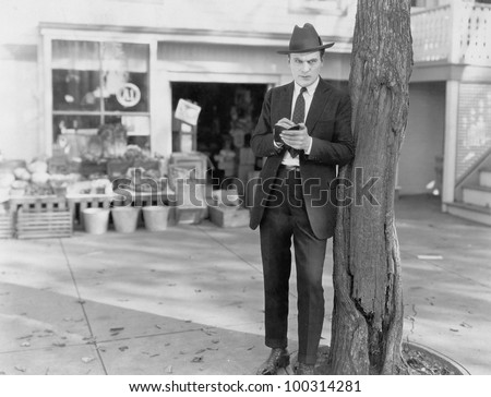 Detective leaning against tree taking notes - stock photo